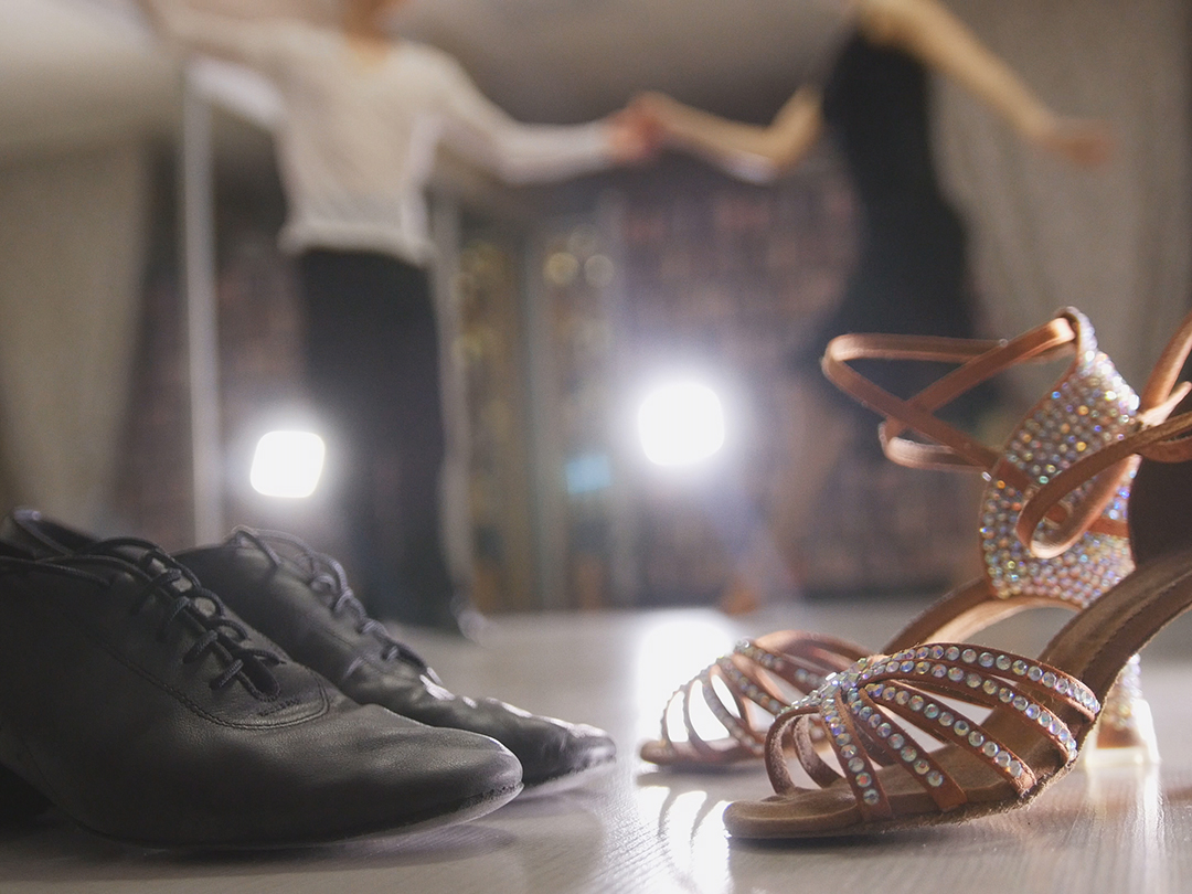 Dance shoes with people dancing in the background.
