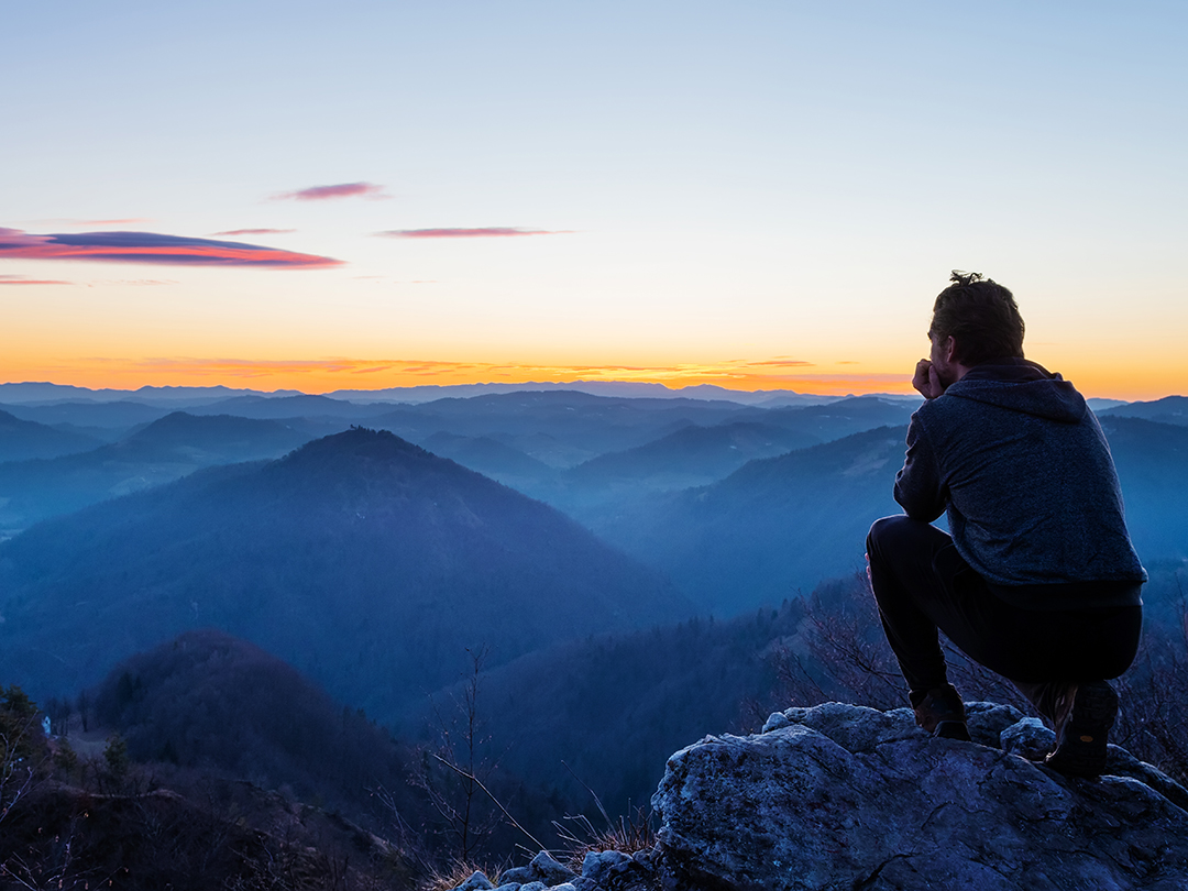 A man sits on top of a mountain look out at the view.