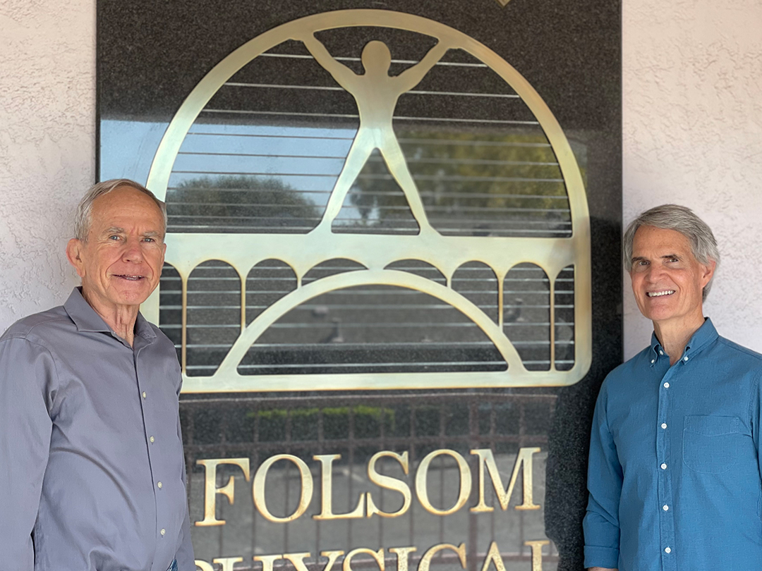 Tim and Michael smile in front of the Folsom Physical Therapy sign.