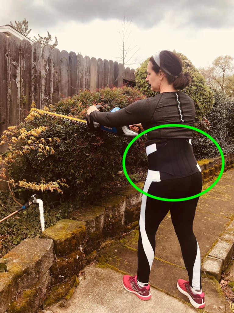 Brigit models the correct way to position your body while using a motorized hedge clipper.