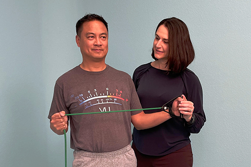 Brigit Lim instructs her patient as he stretches an exercise band with both hands.