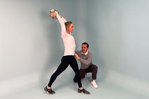 Eric coaches a patient through throwing a soccer ball.