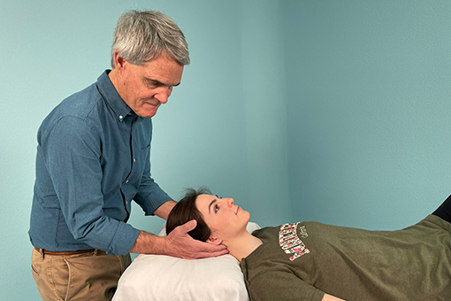 Tim McGonigle gently holds a patient's head and neck.