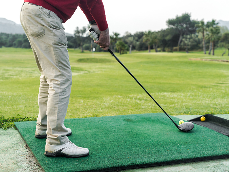A golfer positions himself to swing a golf club.