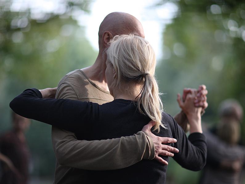 A man and woman ballroom dance outdoors.