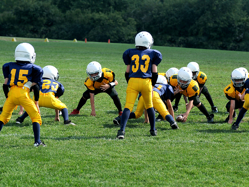 Children play football on a field.