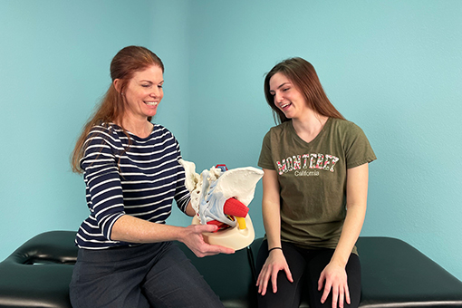 Kristen Branham shows a female patient a pelvic floor model.