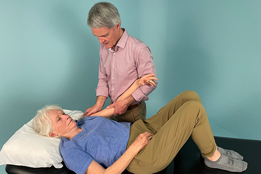 Tim McGonigle treats a patient's arm as she lies on a table.