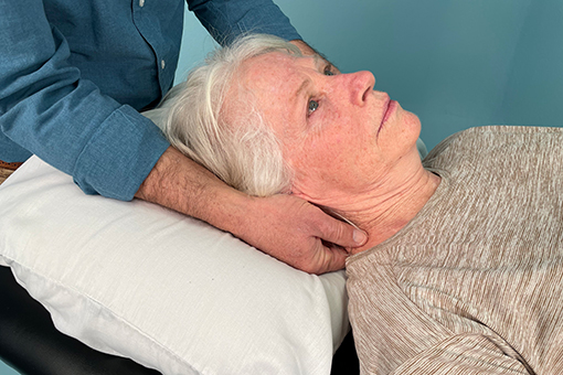 Tim McGonigle's hands rub his patient's neck while her head rests on a pillow.