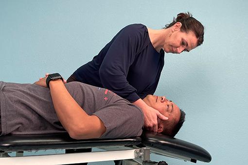 Brigit treats a patient's neck while he lies on a treatment table.