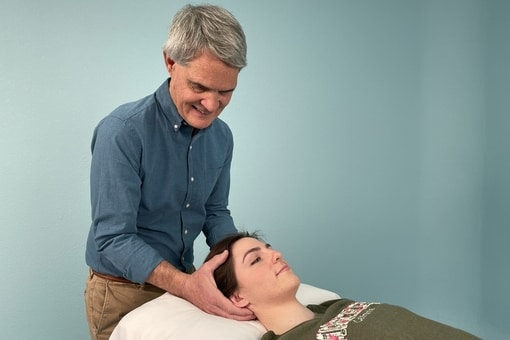 Tim treats a patient's head.
